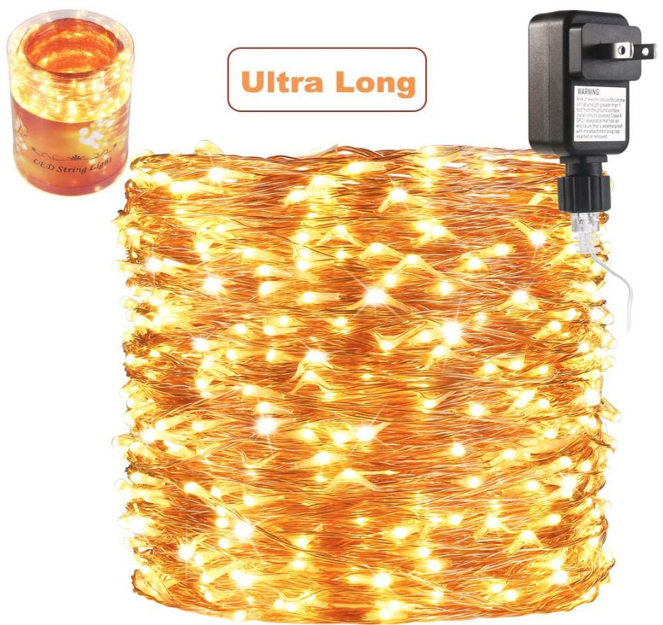 A coil of gold string lights with the plug shown above them.