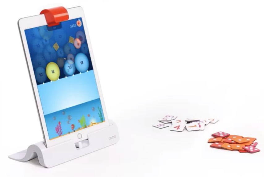The numbers game is open on the Osmo app on a tablet. Small tiles are piled in front of the tablet.
