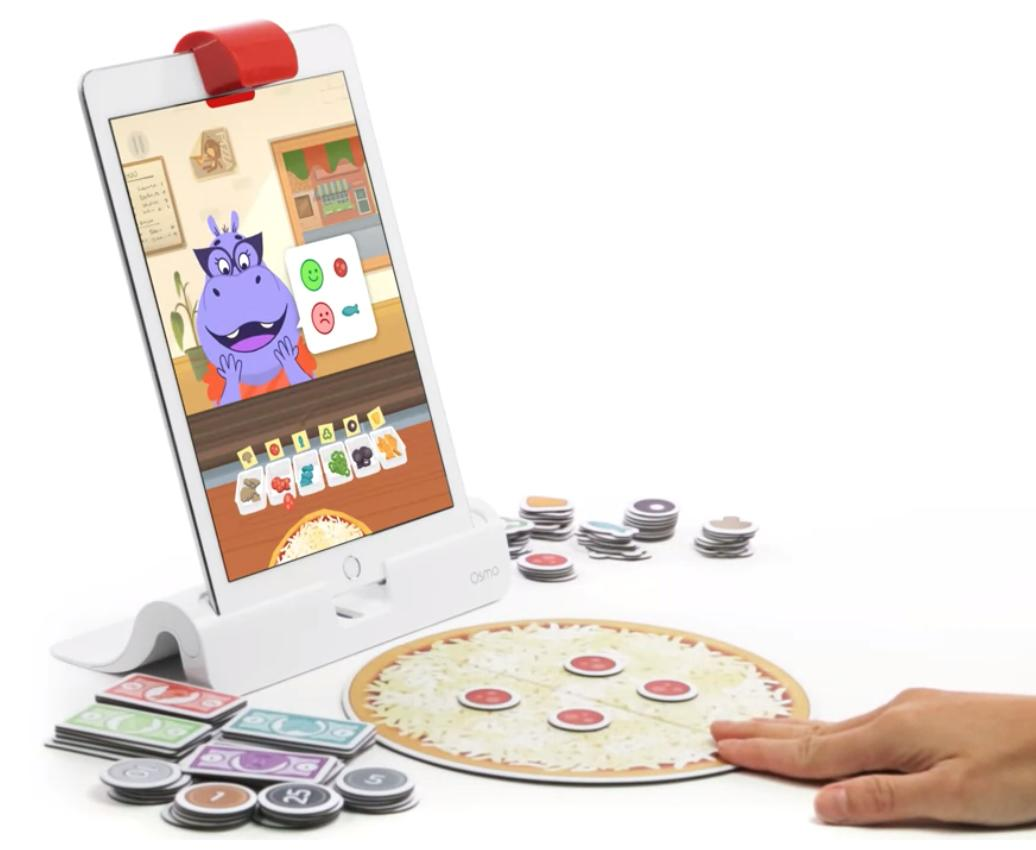 The Pizza Co game is open on a tablet with a pizza, toppings, and money for change in stacks in front of it.