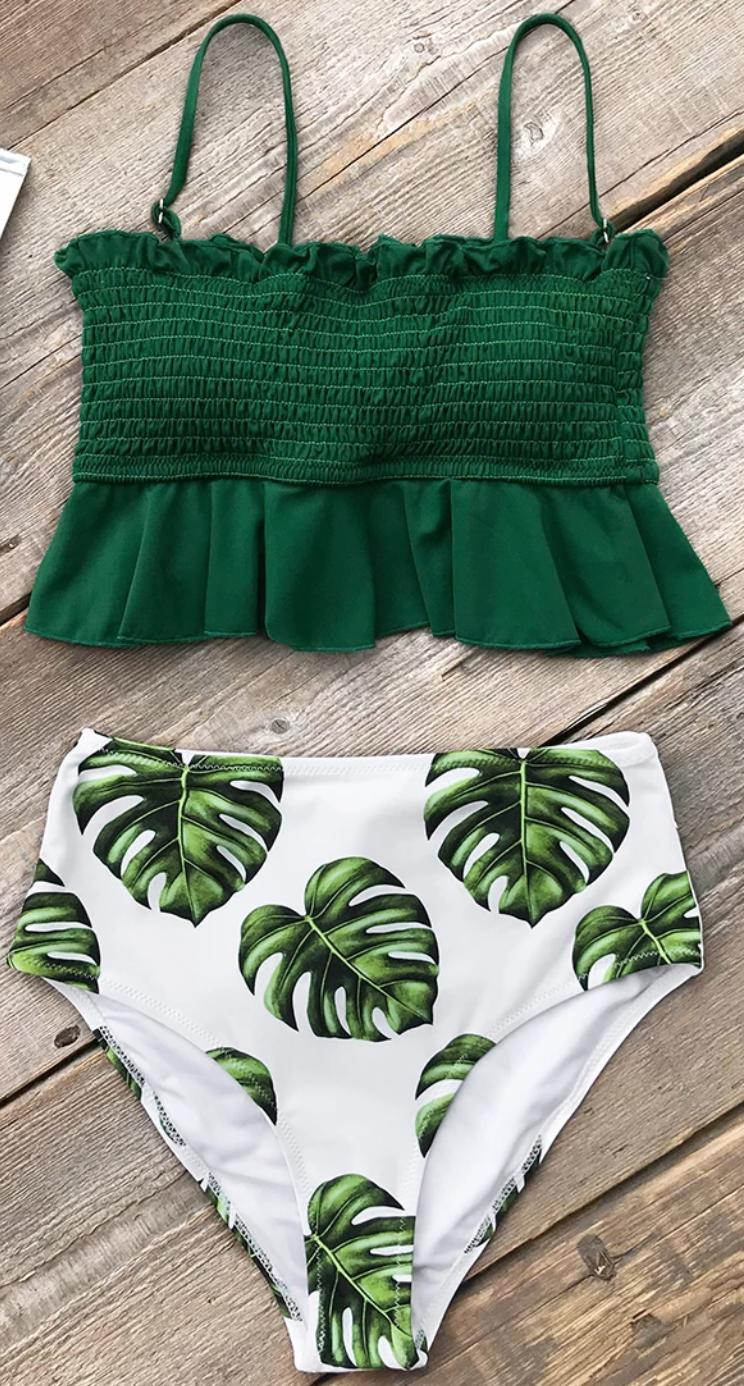 A green and white high waisted bikini swimsuit on a wood background.