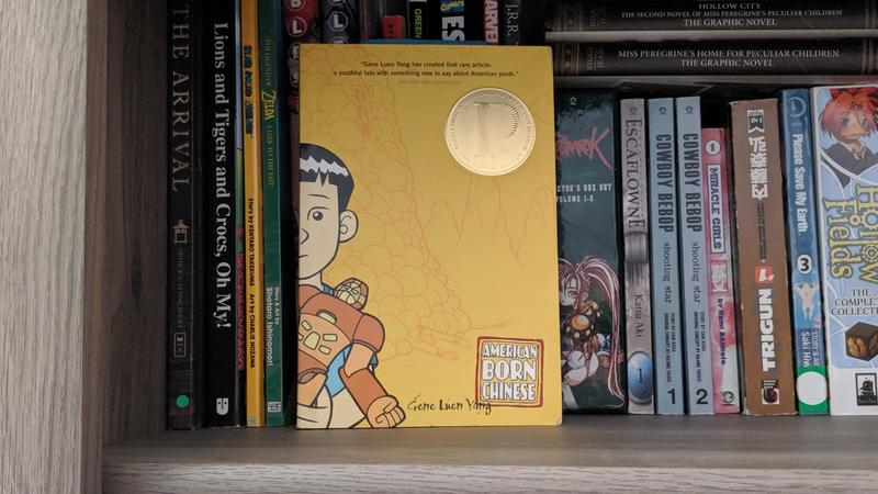 A chinese boy is on the cover of American Born Chinese. It sits on a bookshelf.