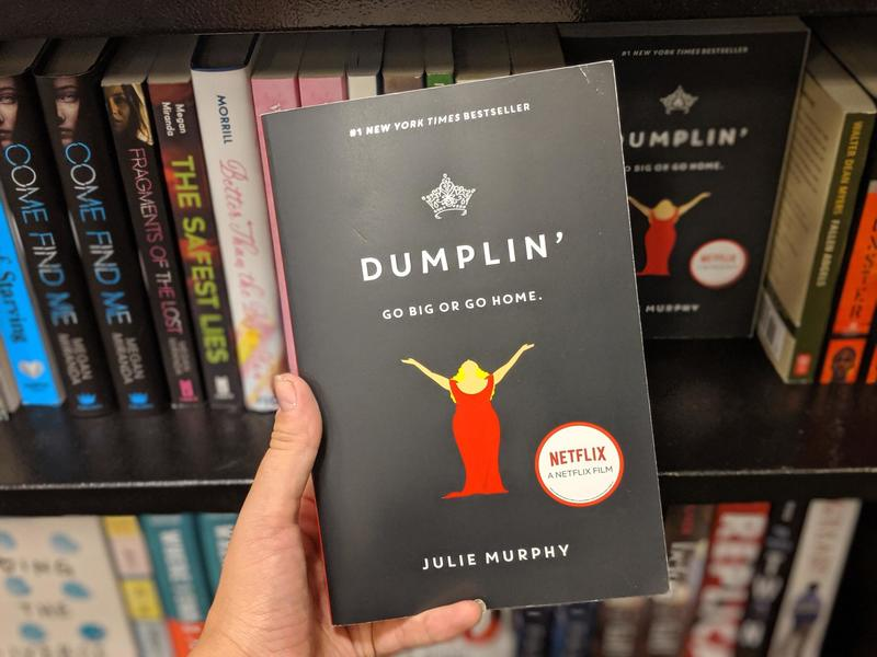A black covered copy of Dumplin is held in front of a bookshelf