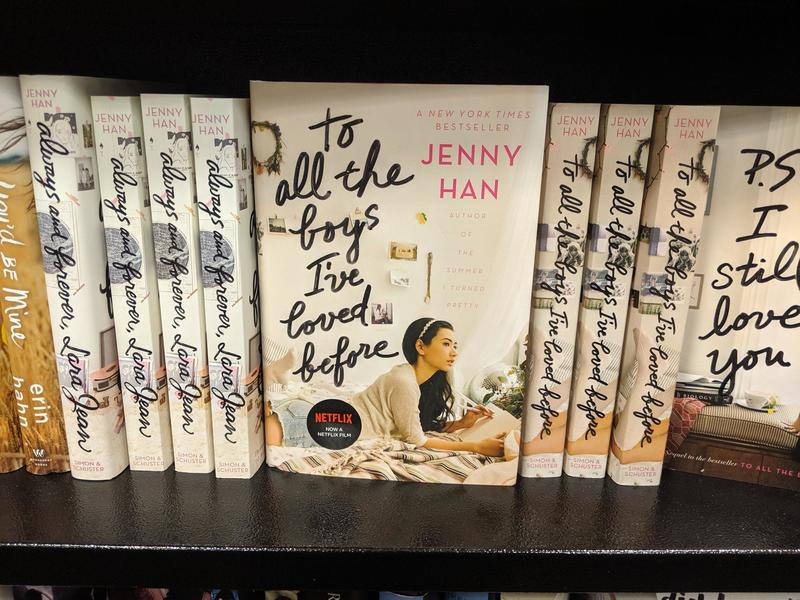 Multiple copies of To All the Boys I've Loved Before are on a bookshelf.