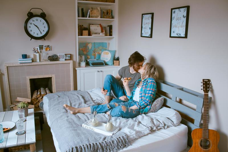A heterosexual couple sit and kiss on a bed.