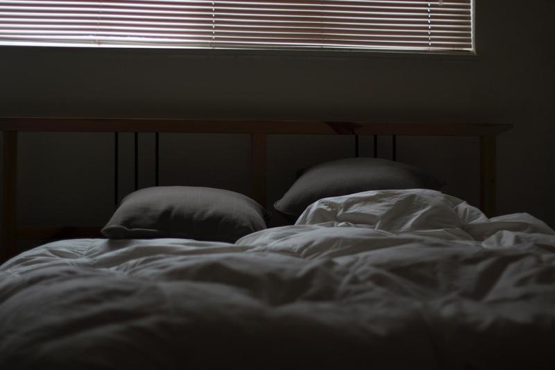 An empty bed with messed up sheets.