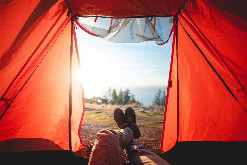 A pair of feet are extended ut of a tent with nature in the background.