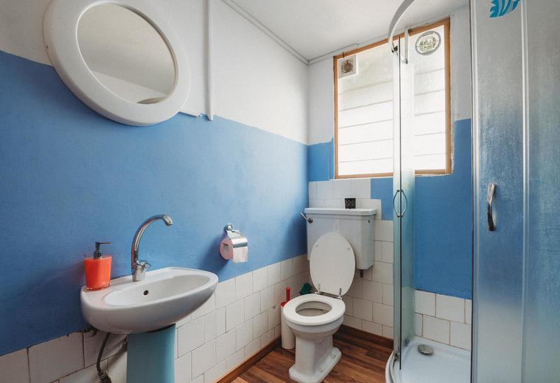 A narrow bathroom decorated in white and blue.
