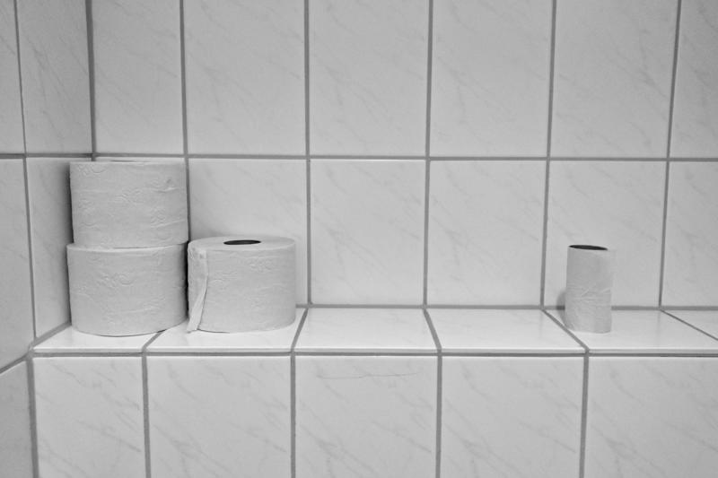 Several rolls of toilet paper sit on white tiles.