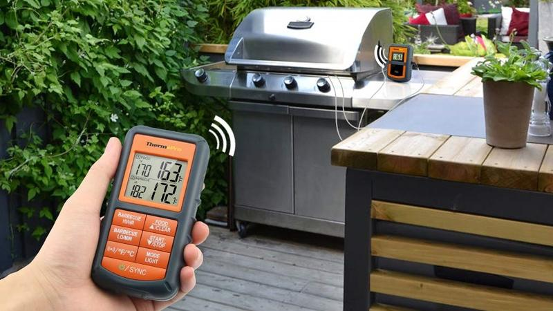 A hand holds up the Thermopro TP08 meat thermometer in front of a grill.