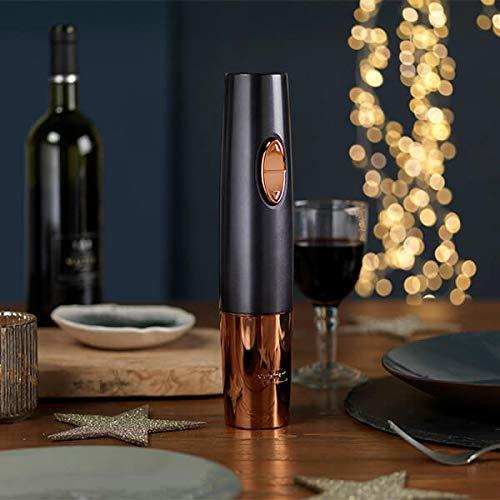 The Cuisinart Wine Opener sits on a dinner table with glasses and a wine bottle in the background.