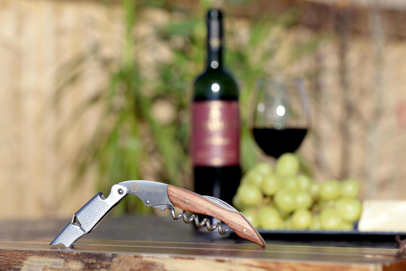 The Highcoup Corkscrew is open on a table with a bottle and glass of wine in the background.