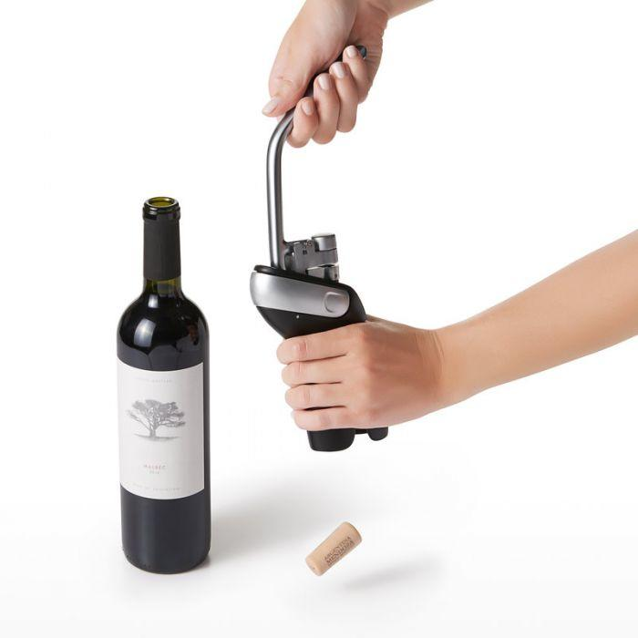 A pair of disembodied hands use the OXO wine opener while another wine bottle sits next to it.