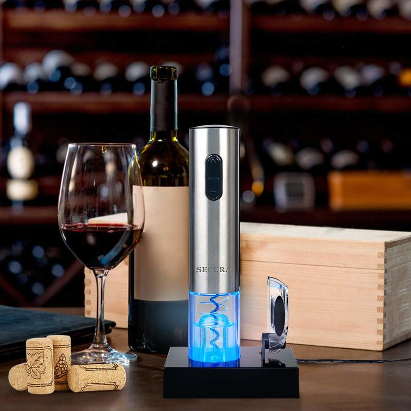 A wine opener sits on the bar next to corks, a glass of red wine, a bottle of wine and some boxes.