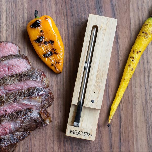 The Meater+ thermometer sits in its case on a wood table next to veggies and cooked meat.