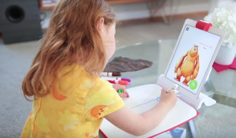 A child plays with the creative kit, drawing on the included board.