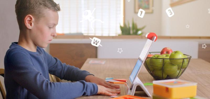 A child sits at an Osmo enabled tablet playing a game. Letters fly in the air around them.