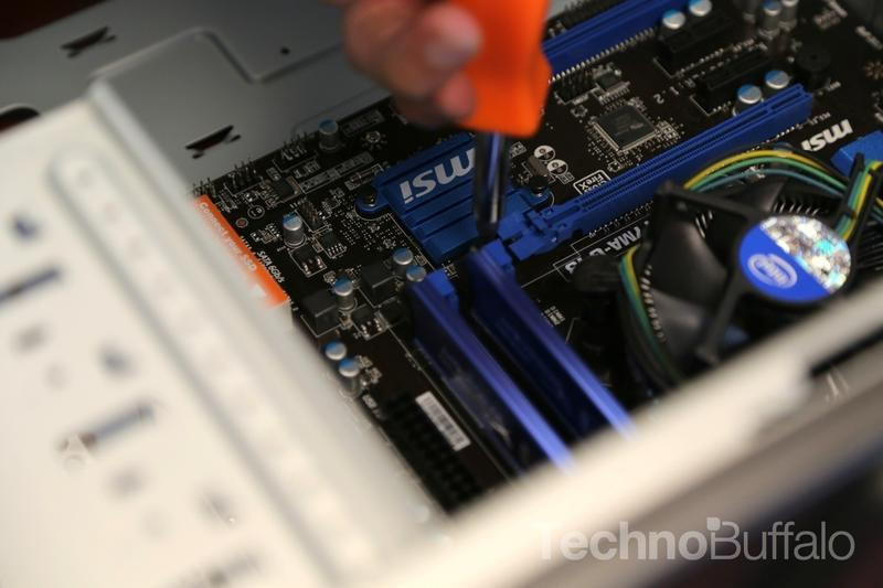 Screwing in the motherboard.