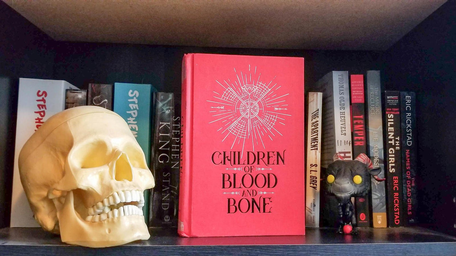 A red covered book sits on a bookshelf with a skull and a funko pop.